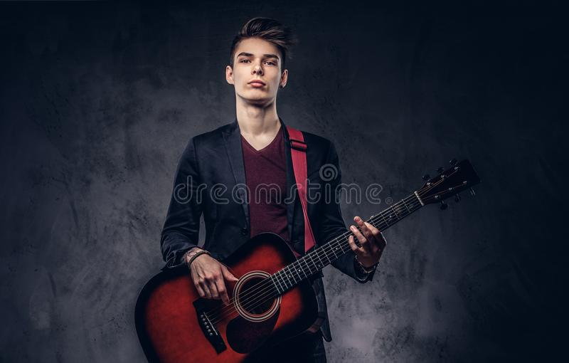 Stylish young musician with stylish hair in elegant clothes, playing on an acoustic guitar. Stylish young musician with stylish hair in elegant clothes with a royalty free stock image