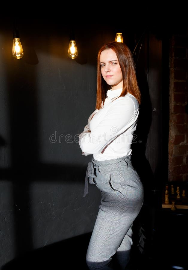 Stylish young red-haired girl stands in doorway of the loft interior on the background of hanging glowing bulbs royalty free stock image
