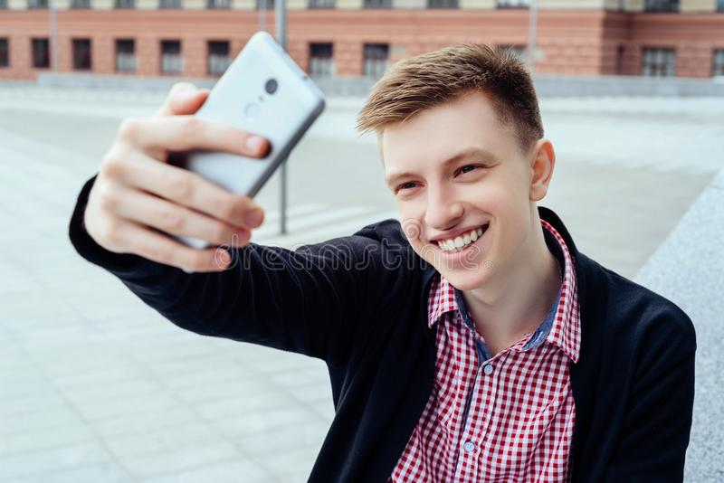 Stylish young smiling man in plaid shirt making selfie outdoors. Technology and communication concept, people, person, phone, portrait, natural, male, mobile stock photos