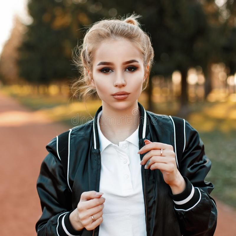 Stylish young woman in a black jacket and white polo shirt. On a sunny day stock photography