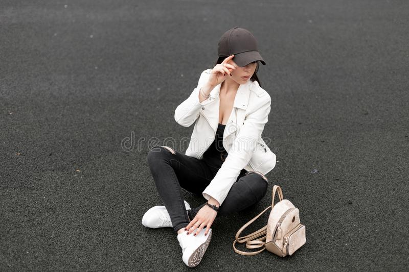 Stylish young woman in black ripped jeans in a leather jacket in a t-shirt with a gold backpack in fashionable sneakers. In a trendy baseball cap sits on the royalty free stock photo