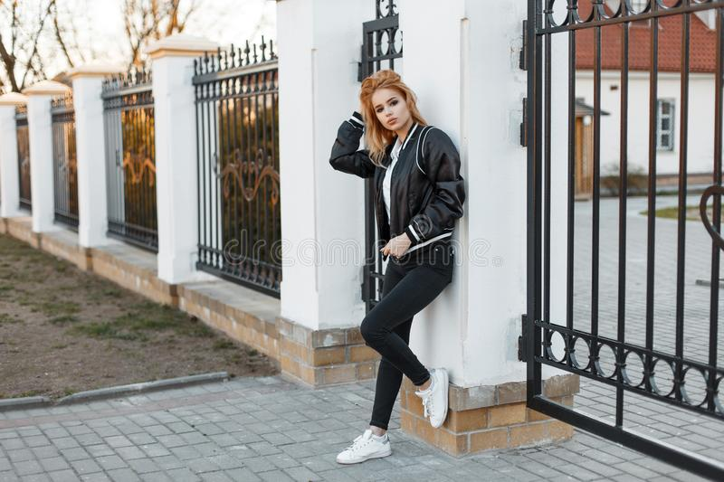 Stylish young woman in a black spring jacket in trendy jeans in a white polo shirt in sneakers posing near a vintage metal fence. American stylish girl royalty free stock photo