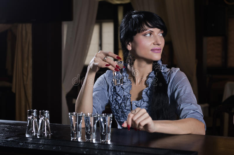 Stylish young woman drinking alone at the bar stock photos