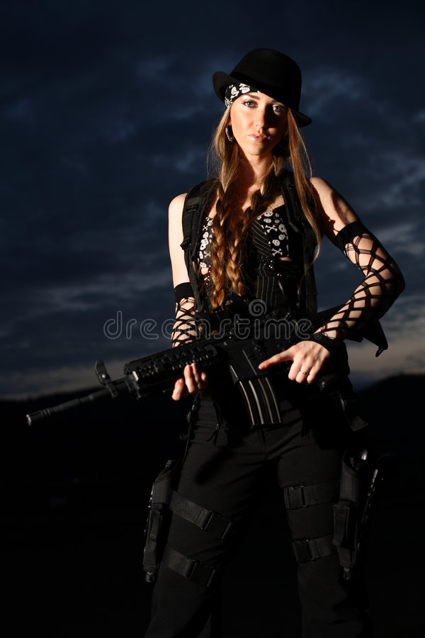 Stylish young woman with gun royalty free stock photo