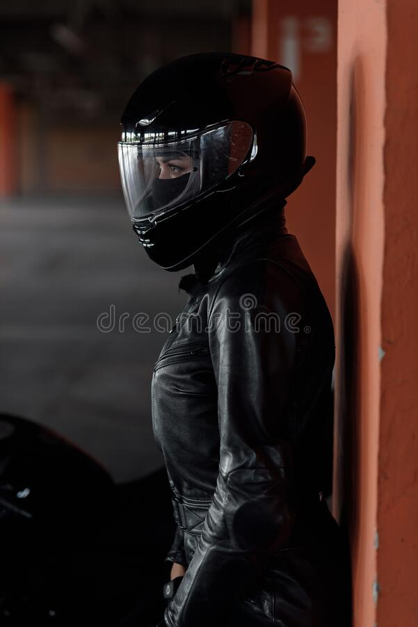 Free Stylish Young Woman Motorcycle Rider In Black Protective Gear And Full-face Helmet Near Her Bike On Underground Parking. Royalty Free Stock Images - 194618589