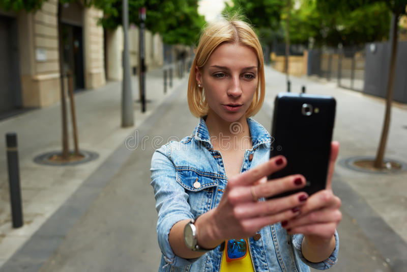 Stylish young woman photographing urban view with mobile phone camera during summer journey royalty free stock photography