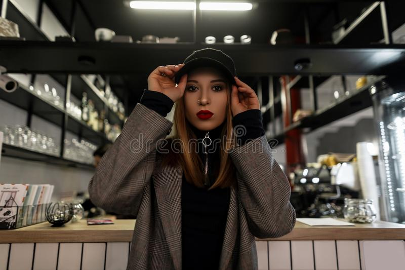 Stylish young woman with a pierced nose in a trendy black cap in a gray vintage checkered jacket with red lips posing at the bar. Modern fashionable girl royalty free stock photo