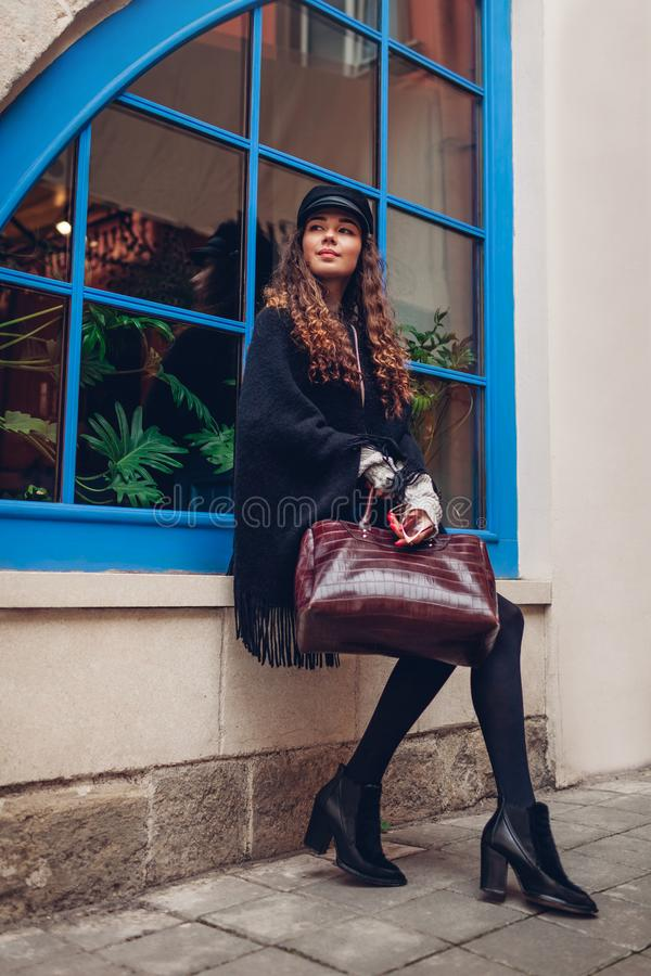 Stylish young woman posing against blue window outdoors. Fashionable outfit. Beautiful model smiling. Stylish young woman posing against blue window outdoors royalty free stock images