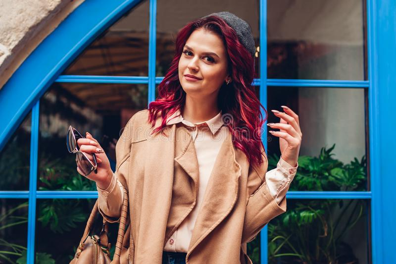Stylish young woman posing outdoors. Fashionable autumn outfit. Happy beautiful model wearing accessories royalty free stock photography
