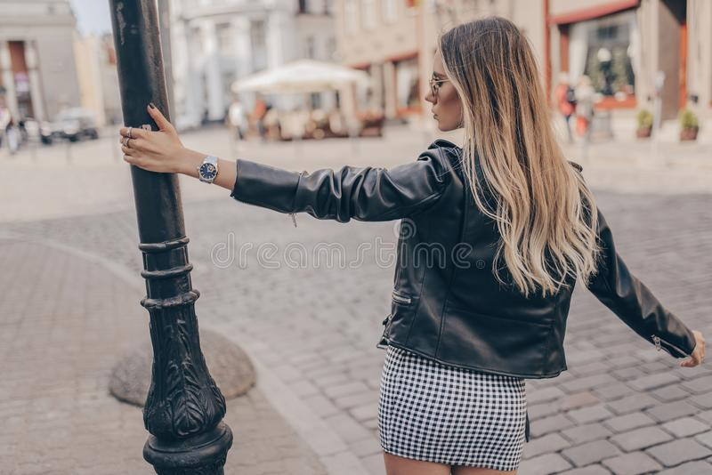 Stylish young woman posing with watch in the street royalty free stock photo