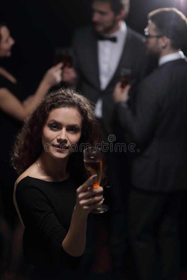 Stylish young woman raising a glass of champagne royalty free stock images