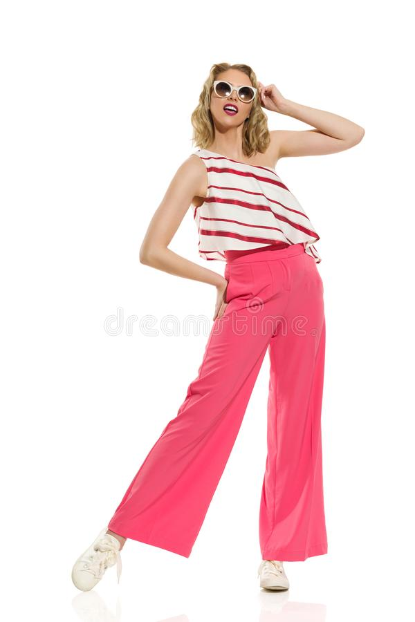 Stylish Young Woman In Red Wide Leg Trousers And Sunglasses royalty free stock image