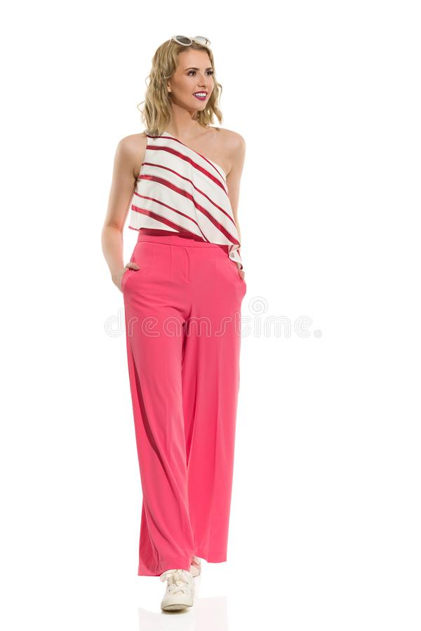 Stylish Young Woman In Red Wide Leg Trousers Is Walking Towards Camera. Fashion model in red wide leg trousers and striped top is walking towards camera and royalty free stock photos