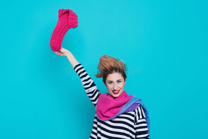 Stylish young woman removes a knitted pink hat from her head in the studio on a blue background. Winter goodbye. Spring comes. Lif royalty free stock image
