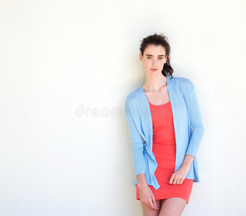 Stylish young woman standing alone against white wall royalty free stock photo