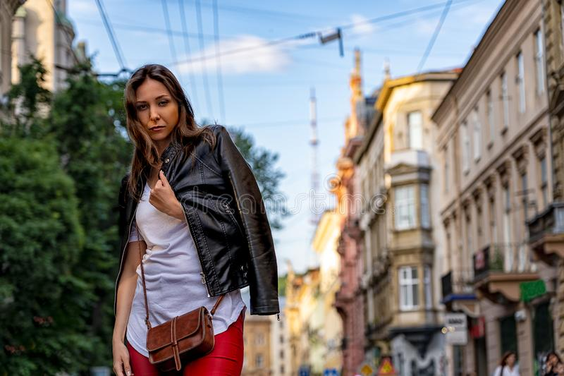 Stylish young woman is standing on the street of Lviv. Street fashion photography with beautiful girl stock photography