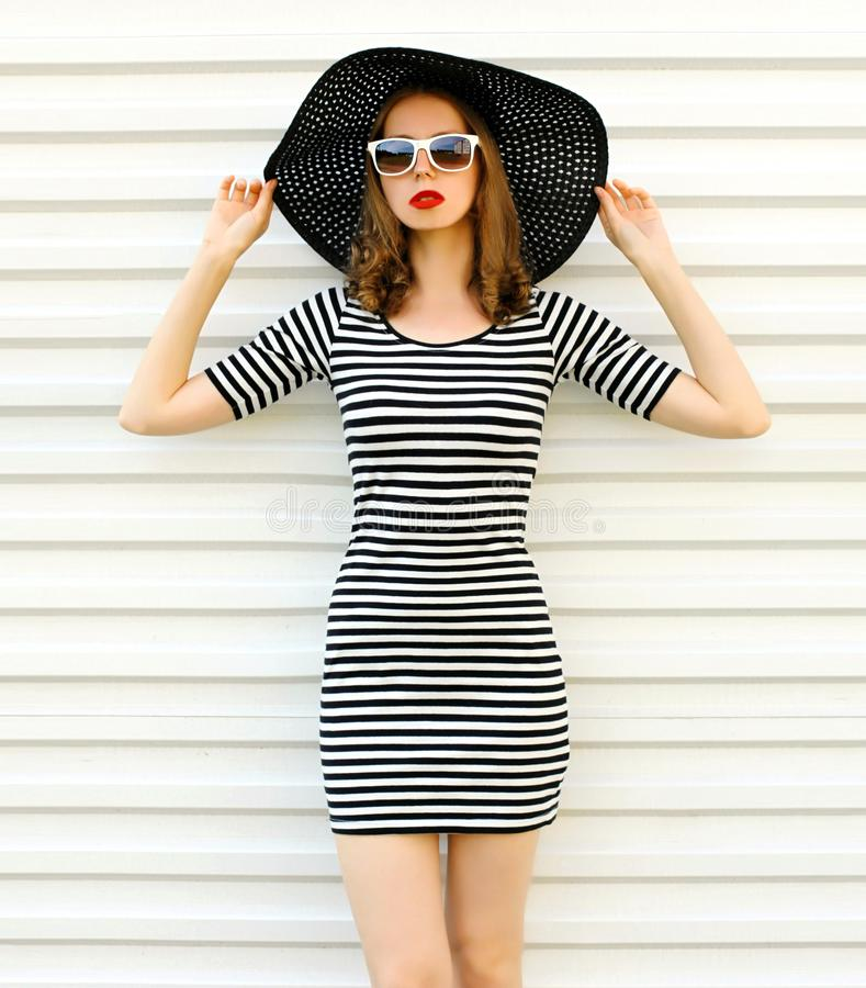 Stylish young woman in striped dress, summer straw hat posing on white wall. Background royalty free stock images