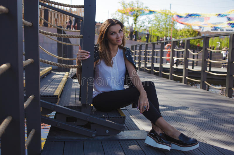Stylish young woman on summer city walk, sitting on the stairs royalty free stock photo