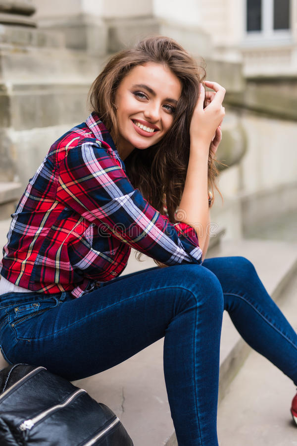 Stylish young woman on summer city walk sitting on the stairs stock photography