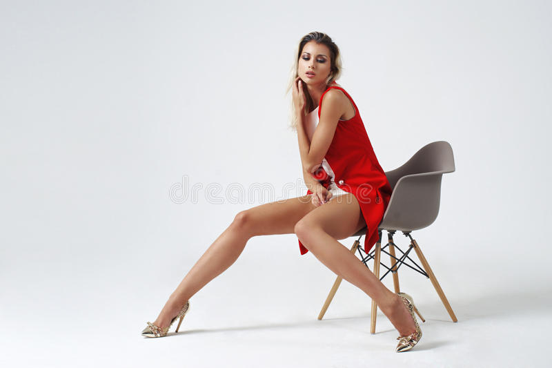 Stylish young woman in white dress and red jacket. Young beautiful stylish woman posing in white short dress and red jacket on bright gray background. Studio royalty free stock photography