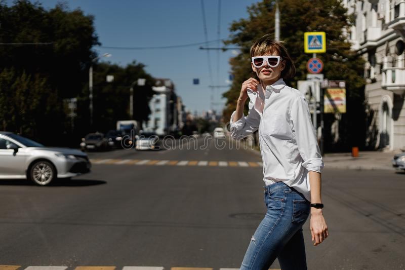 Stylish young woman in white sunglasses dressed in white shirt and jeans is crossing in a city on a summer sunny day.  stock photo