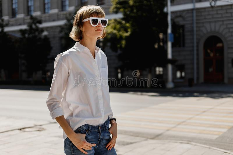 Stylish young woman in white sunglasses dressed in white shirt and jeans is standing in the city street on a summer stock photos