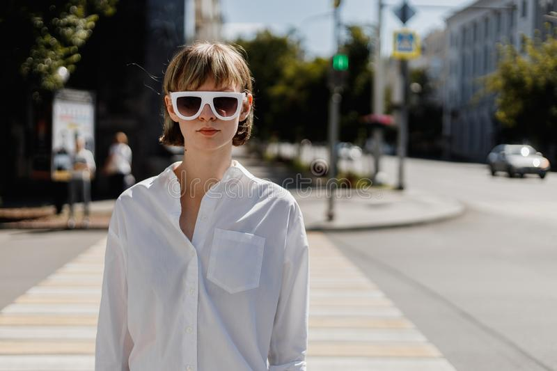 Stylish young woman in white sunglasses dressed in white shirt is standing in the city street on a summer sunny day stock images