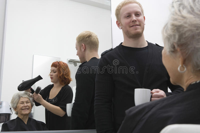 Stylist Blow Drying Senior Woman's Hair In Salon stock photography