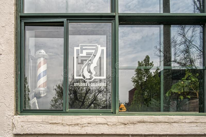 Stylist colorists & barber sign. American barber pole sign with a helical stripe red, white, and blue  in a window  of a commerce stock photos