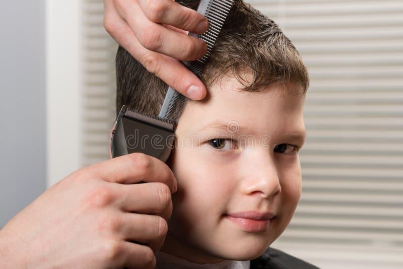 Stylist cuts the boys hair with a hair clipper in barbershop. Stylist cuts the boy`s hair with a hair clipper in barbershop stock image