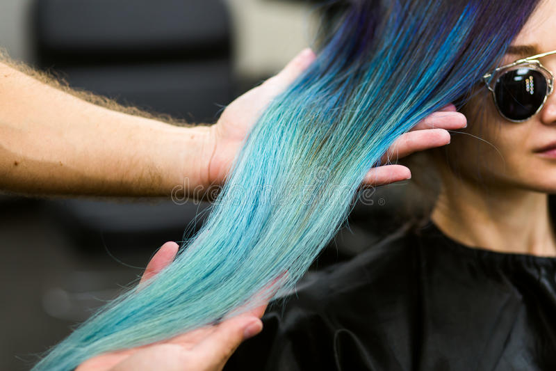 Stylist demonstrates his work with Beautiful girl. Barber haircut dyed hair color blue stock image
