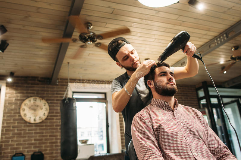 Stylist drying clients hair at salon free space stock photography