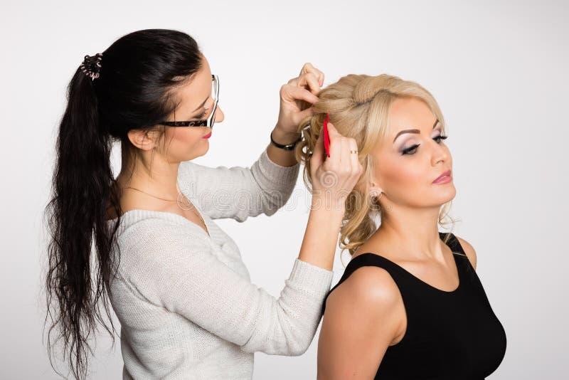 Stylist-frisören gör hår som utformar den blonda flickan royaltyfri foto