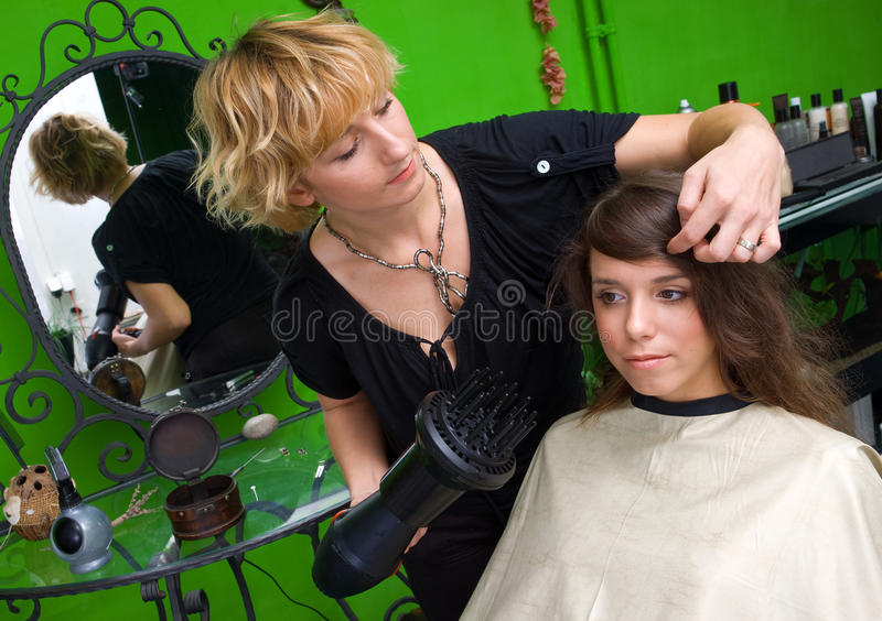 Stylist with hair dryer working royalty free stock photos