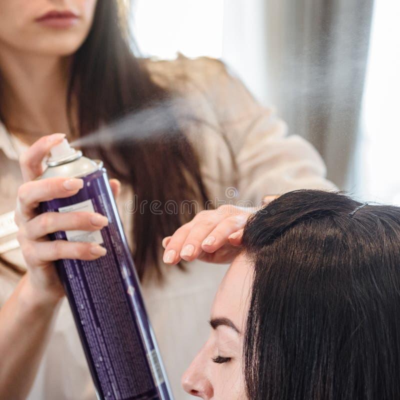 Stylist with hair spray. Stylist using hair spray to fix modern hairstyle stock photo