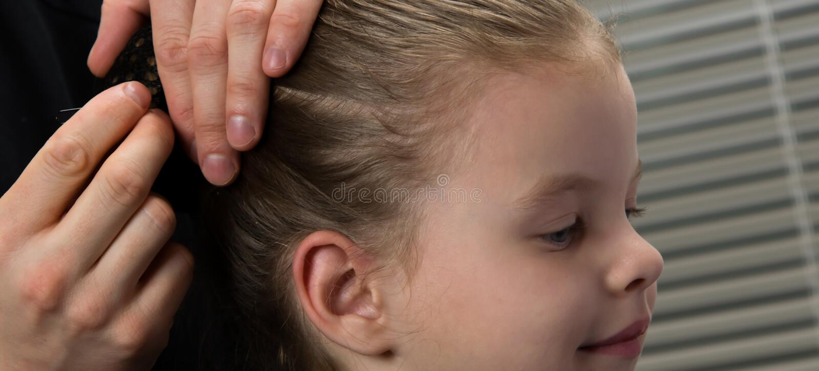 Stylist hairdresser. creates a hairstyle for the evening, a little girl, stabs hair with a hairpin. royalty free stock photos