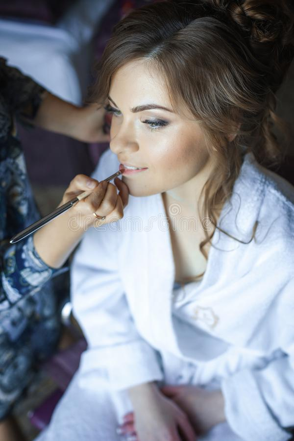 Stylist makes make-up girl on wedding day royalty free stock image