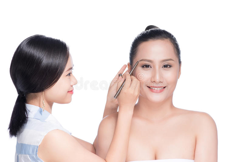 Stylist makes professional eye makeup. Beautiful asian model. stock photos