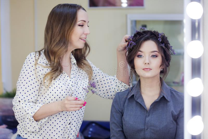 Stylist makeup artist doing makeup and hair in a beauty salon. Professional make-up royalty free stock photography