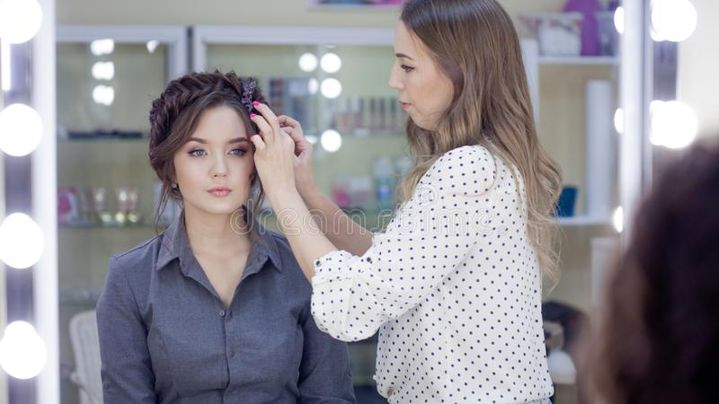 Stylist makeup artist doing makeup and hair in a beauty salon. Professional make-up stock photo