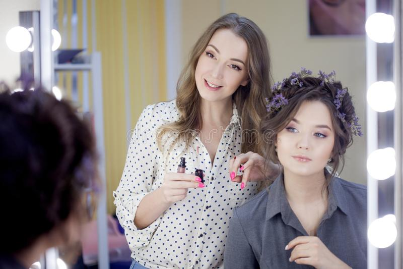 Stylist makeup artist doing makeup and hair in a beauty salon. Professional make-up royalty free stock photo