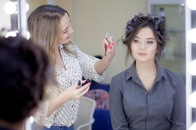 Stylist makeup artist doing makeup and hair in a beauty salon. Professional make-up stock images
