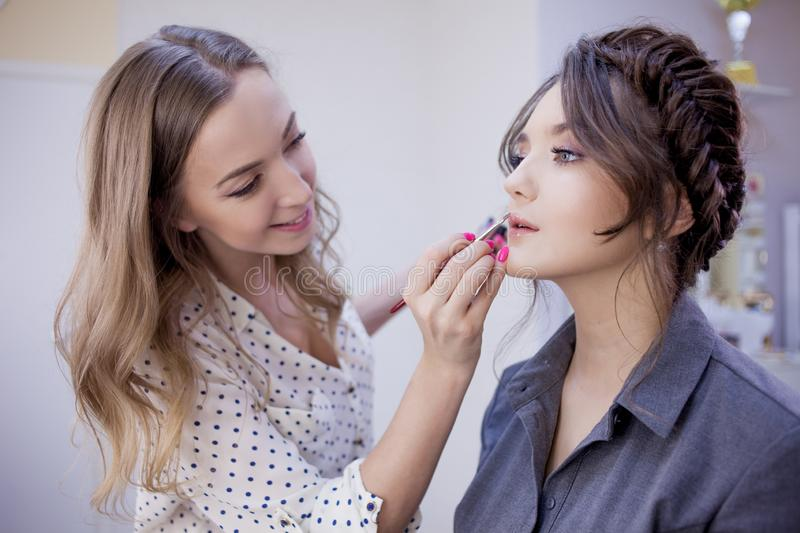 Stylist makeup artist doing makeup and hair in a beauty salon. Professional make-up stock photography