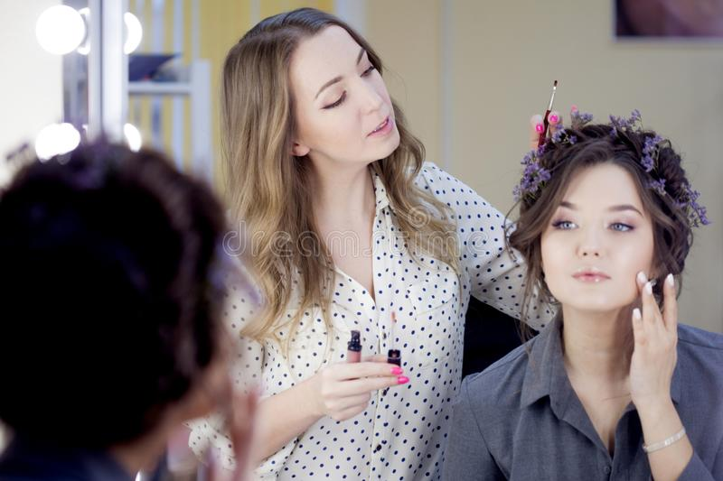 Stylist makeup artist doing makeup and hair in a beauty salon. Professional make-up stock photos
