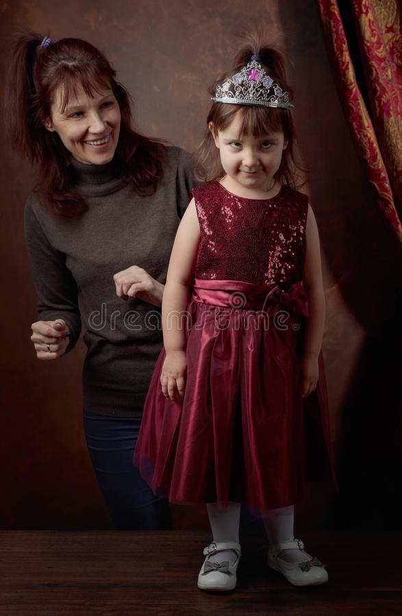Stylist preparing a little girl for the first photo shoot . Little girl posing in red evening dress royalty free stock photo