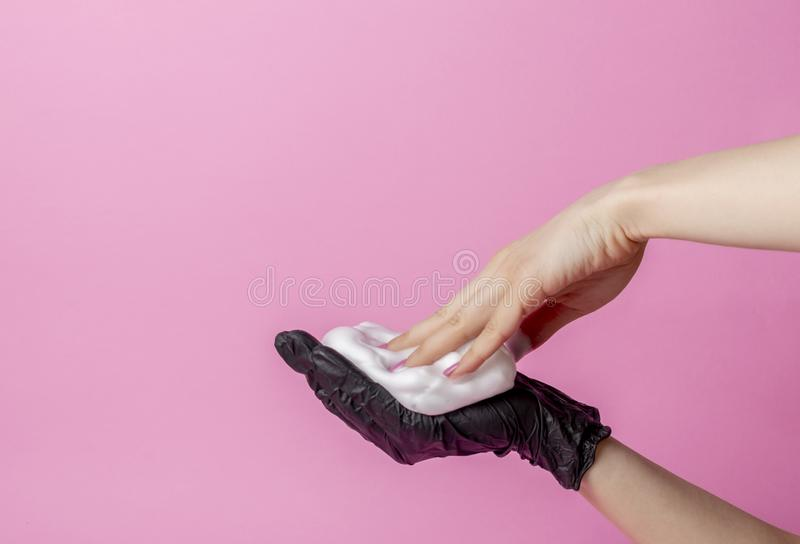 The stylist`s hand in a black glove holds a hairbrush. the second hand takes the foam. hair care concept stock image