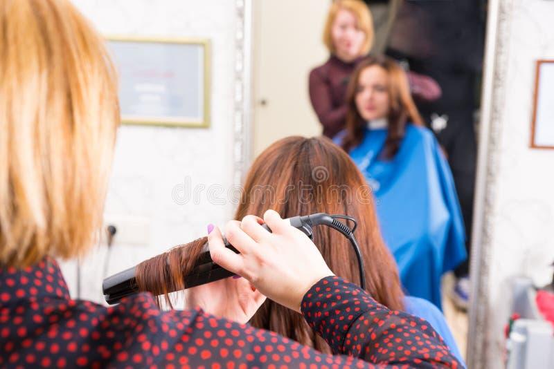 Stylist som framlänges använder järn för att utforma hår av klienten royaltyfri bild
