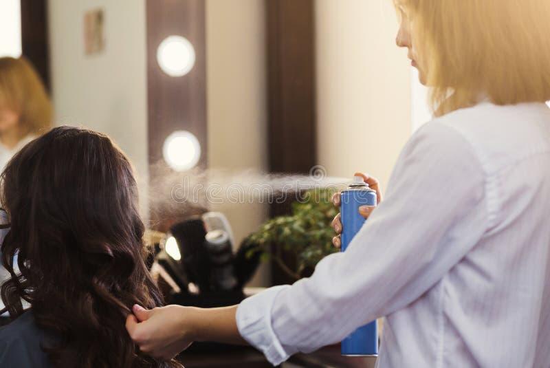 Stylist som gör den lockiga frisyren på skönhetsalongen royaltyfria bilder