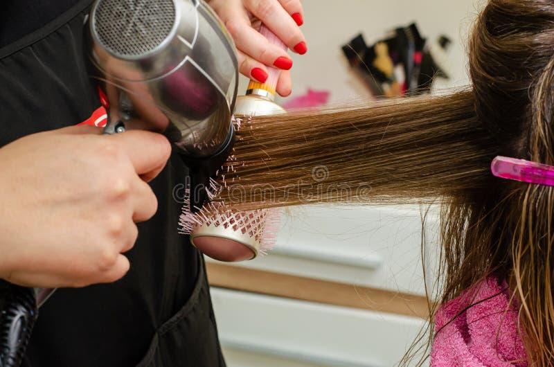 Stylist torkar klientens hår med hårtork och pensel royaltyfria foton