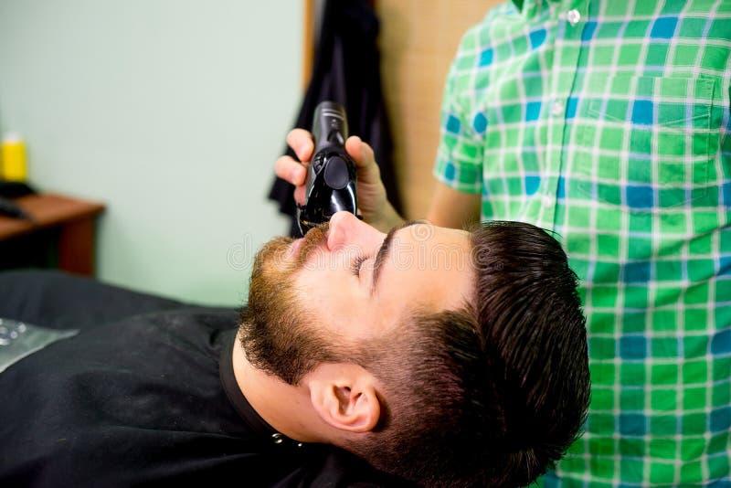 Stylist trimming beard stock photo